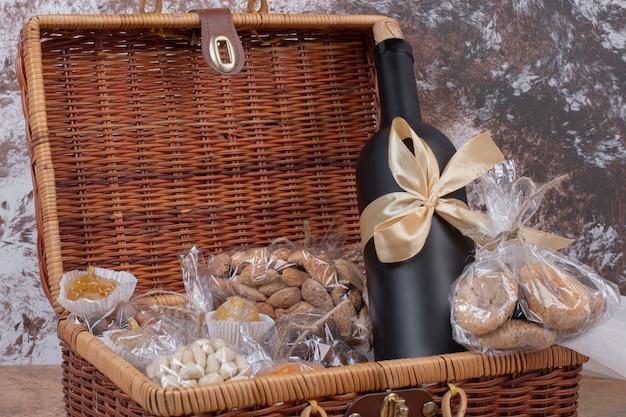 Gedroogd fruit en noten verpakt in plastic zakken met houten zak met fles wijn.