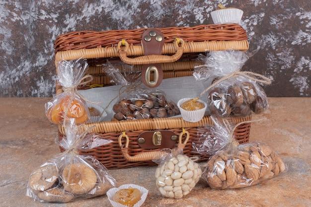 Gedroogd fruit en noten verpakt in plastic zakken met houten zak.