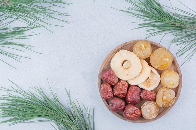 Gedroogd fruit en zilverbes op houten plaat.
