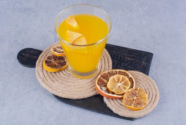 Gedroogd fruit, glas sap en onderzetter op snijplank op marmer.