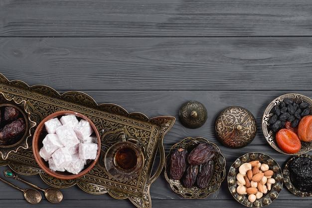 Gedroogd fruit; noten; data; lukum en thee op ramadan over het houten bureau