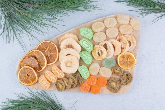 Gedroogd fruit plakjes en marmelade snoepjes op een houten bord.