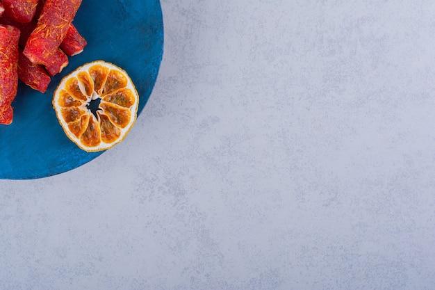 Gedroogd fruitpulp met noten en kaneelstokjes op blauw bord.