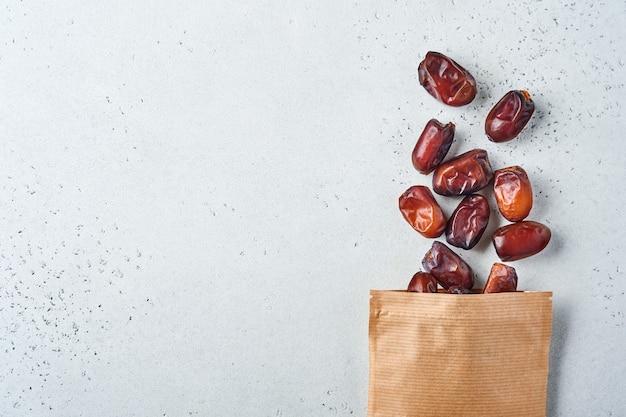 Gedroogd gesneden datumfruit in papieren zak op witte achtergrond. snack veganistisch suikervrij eten.