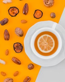 Gedroogde abrikoos; data; amandelen; okkernoot; pinda en hazelnoot met citroenthee cup op gele en witte achtergrond