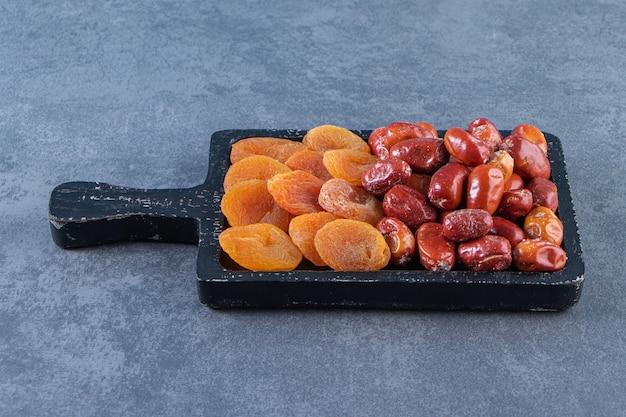 Gedroogde abrikoos en oleaster op een bord, op de marmeren achtergrond.