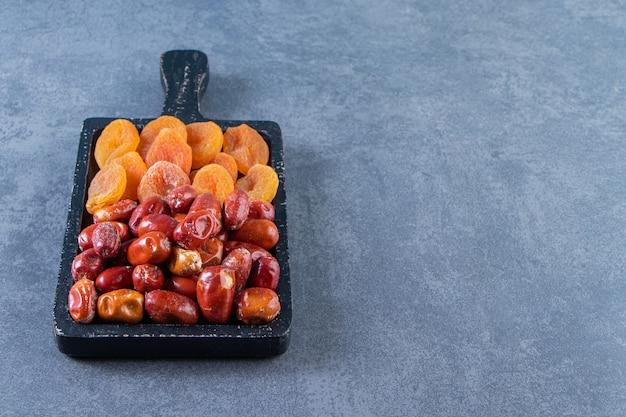 Gedroogde abrikoos en oleaster op een bord, op het marmeren oppervlak