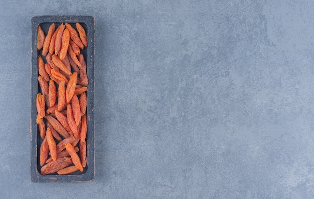Gedroogde abrikoos in de houten plaat, op de marmeren achtergrond.