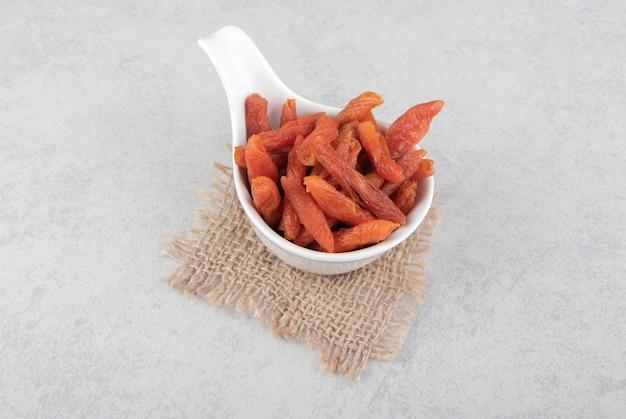 Gedroogde abrikoos in de kom, op de onderzetter, op het marmeren oppervlak