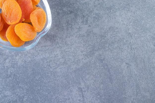 Gedroogde abrikoos in een glazen kom, op de marmeren achtergrond.