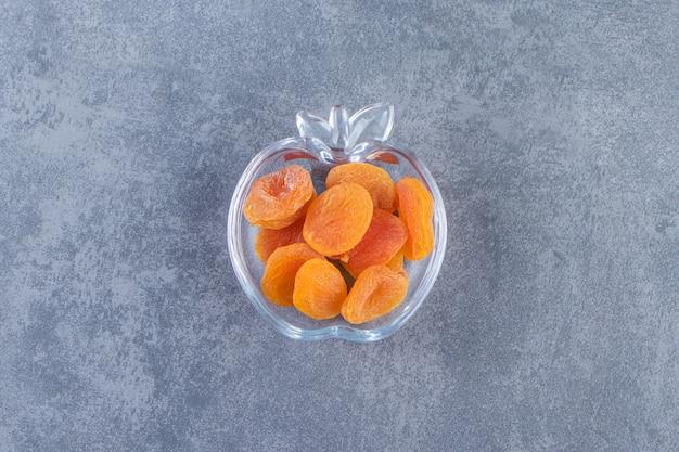 Gedroogde abrikoos in een glazen kom op het marmeren oppervlak