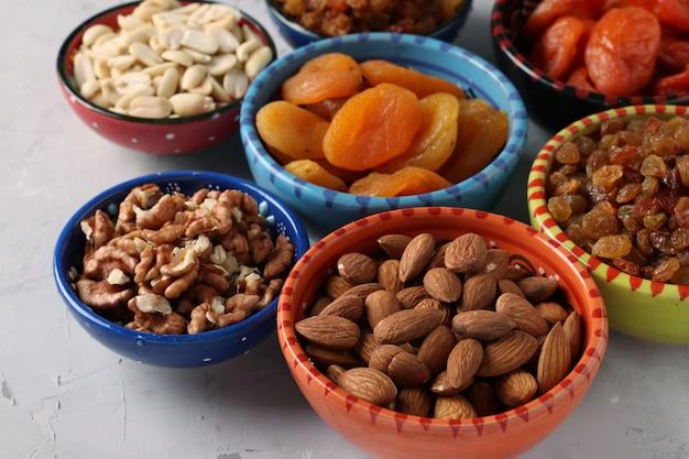 Gedroogde abrikoos, rozijnen, pinda's, amandelen, walnoot in kommen op grijze betonnen tafel