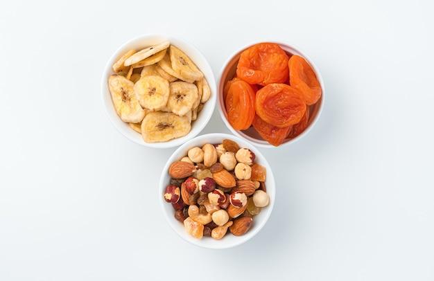 Gedroogde abrikozen, gedroogde banaan en een mengsel van noten en gekonfijte vruchten in drie kopjes op een lichte muur. bovenaanzicht.
