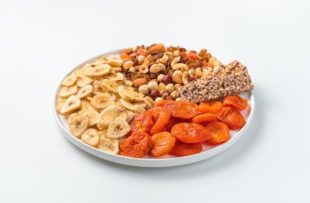 Gedroogde abrikozen, gedroogde bananen, mengsel van noten en mueslireep op een groot bord op witte achtergrond
