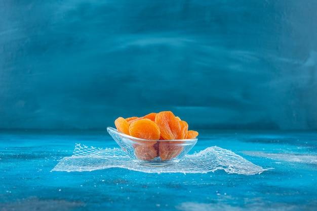 Gedroogde abrikozen in een glazen kom, op de blauwe tafel.