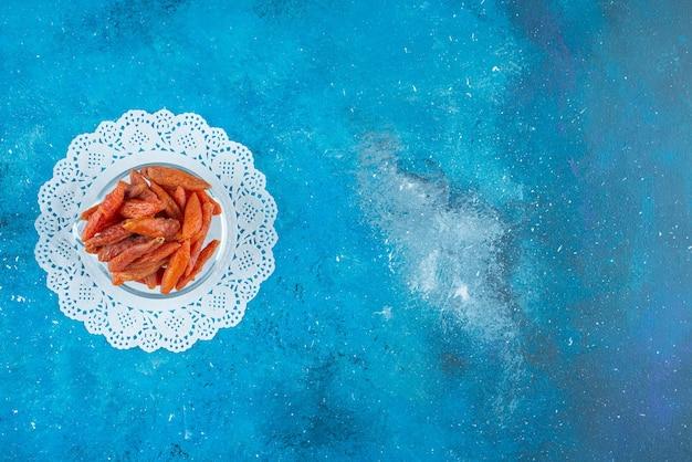 Gedroogde abrikozen in een kom op onderzetter op het blauwe oppervlak