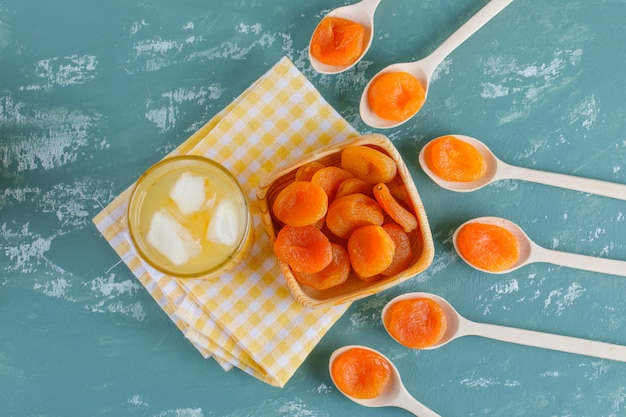 Gedroogde abrikozen in houten plaat en lepels met sap bovenaanzicht op gips en picknick doek