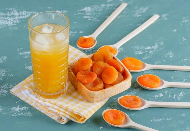 Gedroogde abrikozen met ijzige sap in houten plaat en lepels op gips en picknick doek, bovenaanzicht.