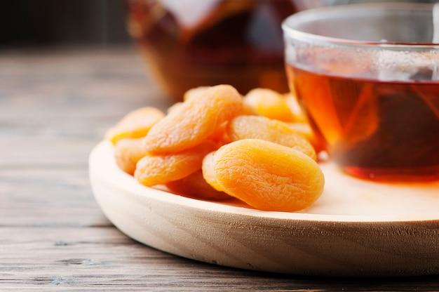 Gedroogde abrikozen met kop zwarte thee