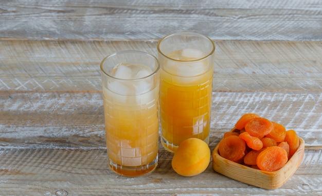 Gedroogde abrikozen met sap, verse abrikoos in een houten plaat op houten tafel, bovenaanzicht.