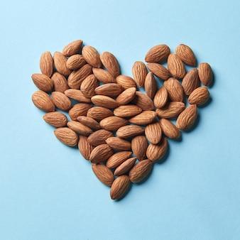 Gedroogde amandelen in de vorm van een hart op een blauwe papieren ondergrond plat leggen. biologisch voedsel