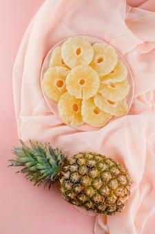 Gedroogde ananas met verse ananas in een plaat op roze en textiel oppervlak