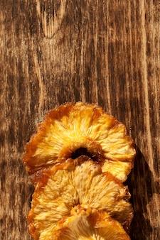 Gedroogde ananas. segmenten op een oud bruin houten bord.