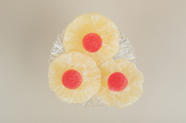 Gedroogde ananasplakken en marmelades op glasplaat