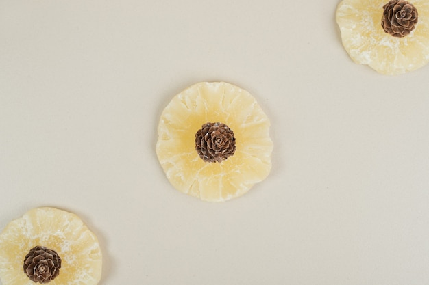 Gedroogde ananasplakken en pinecones op beige oppervlak
