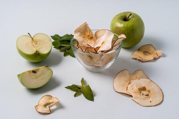 Gedroogde appelchips en verse appels.