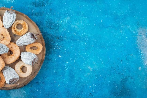 Gedroogde appelringen en persimmon op een bord, op de blauwe tafel.
