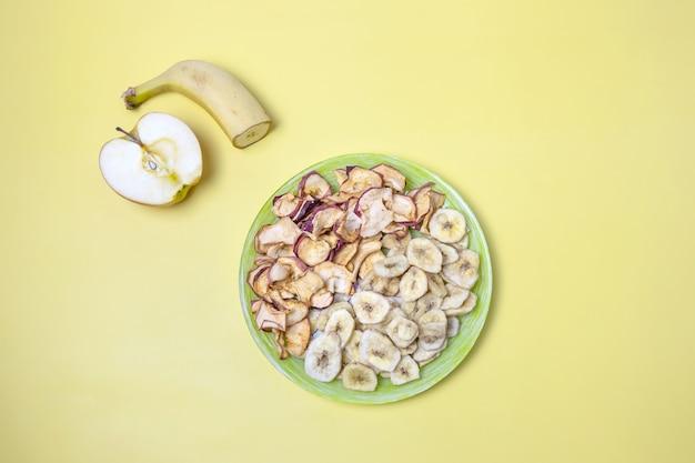 Gedroogde appels en bananen op een bord en verse appel en banaan