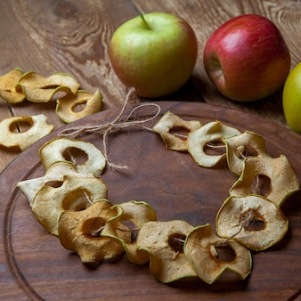 Gedroogde appels op ronde snijplank en verse appels op houten tafel