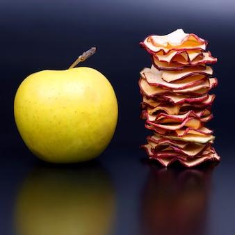 Gedroogde appelschijfjes en verse appel op donkere achtergrond