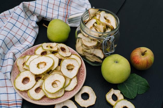 Gedroogde appelschijfjes in open glazen pot. zelfgemaakte biologische gedroogde appelspaanders met verse appel op zwarte lijstachtergrond.