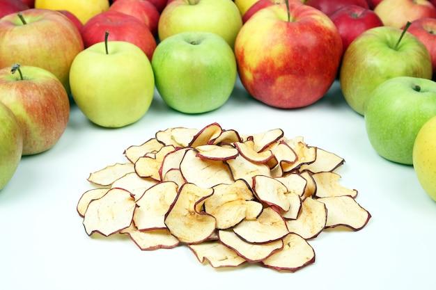 Gedroogde appelschijfjes omgeven door verse appels op witte achtergrond. nuttig vitaminevoedsel