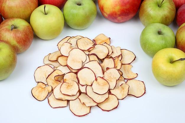 Gedroogde appelschijfjes omgeven door verse appels op witte achtergrond. vitamine en gezonde voeding