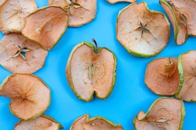 Gedroogde appelschijfjes op blauw