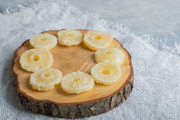 Gedroogde biologische ananasringen geplaatst op een stuk hout