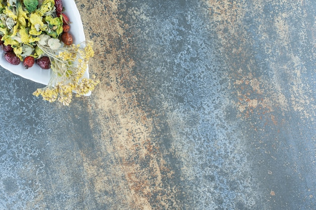 Gedroogde biologische roos en bloemen op bladvormige plaat.