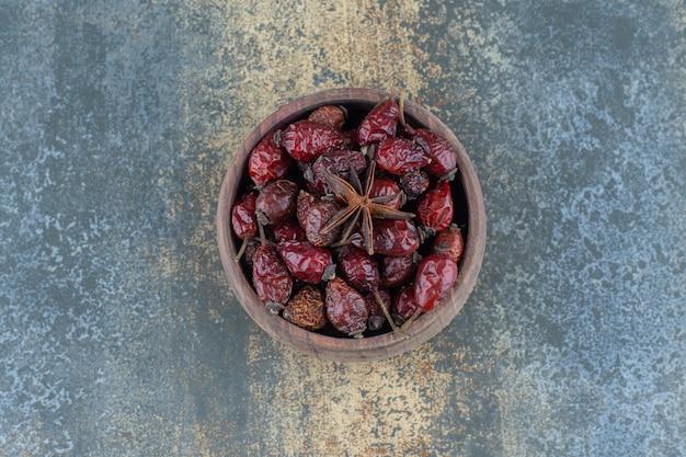 Gedroogde biologische rozenbottels in houten kom.