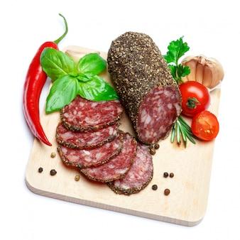 Gedroogde biologische salami worst bedekt met peper op houten portie bord