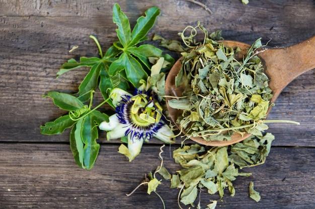 Gedroogde bladeren van passiflora om kalmerende thee op houten achtergrond te drinken
