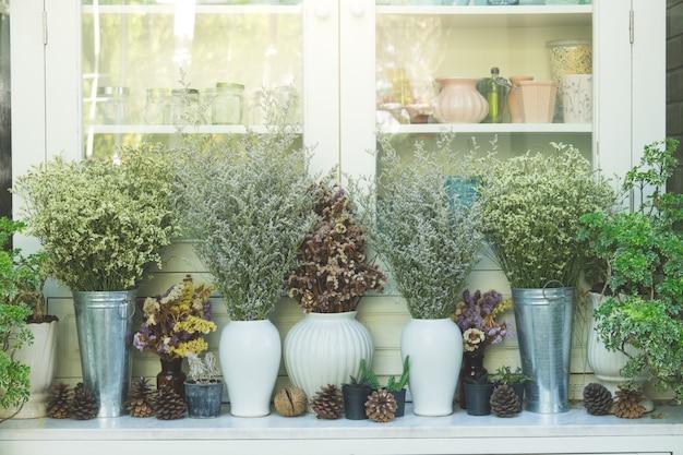 Gedroogde bloem in vintage pot en kruik, versier voor de kast