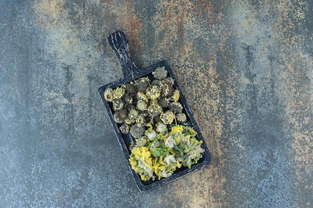 Gedroogde bloemblaadjes op een houten bord.
