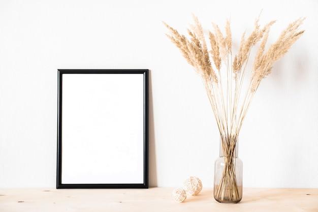 Gedroogde bloemen en een fotolijstje tegen een lichte muur