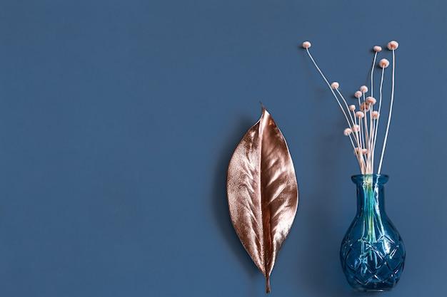Gedroogde bloemen en een vaas op blauw.