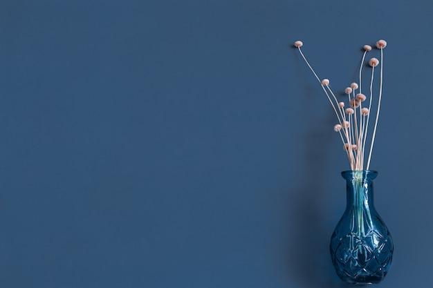 Gedroogde bloemen en een vaas op een blauwe muur.