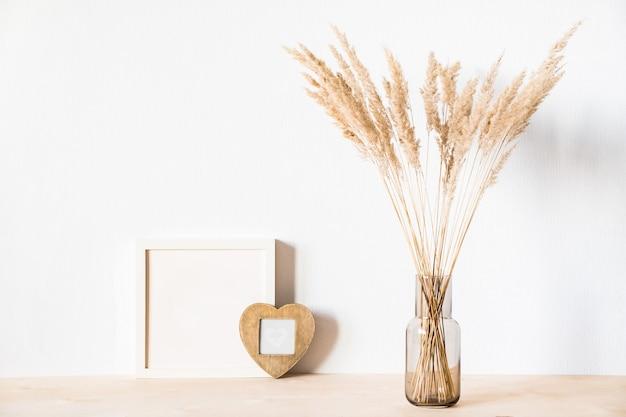 Gedroogde bloemen en fotolijsten tegen een lichte muur