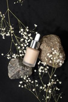 Gedroogde bloemen en make-up foundation met natuurlijke schaduwen op pastel achtergrondstilleven cosmetica voor...